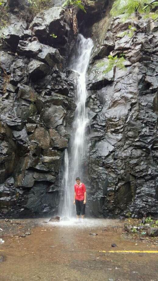 A man enjoying in the artificial waterfall at Kharghar Hills.